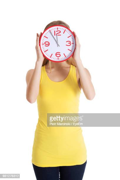 Woman Holding Clock Against White Background