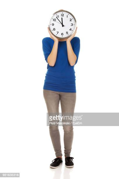 woman holding clock while standing against white background - cadran d'horloge photos et images de collection