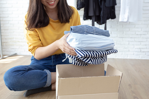 Woman holding Clothes with Donate Box In her room, Donation Concept. 1083939316