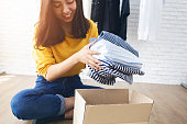 Woman holding Clothes with Donate Box In her room, Donation Concept.