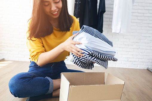Woman holding Clothes with Donate Box In her room, Donation Concept. 1129340852