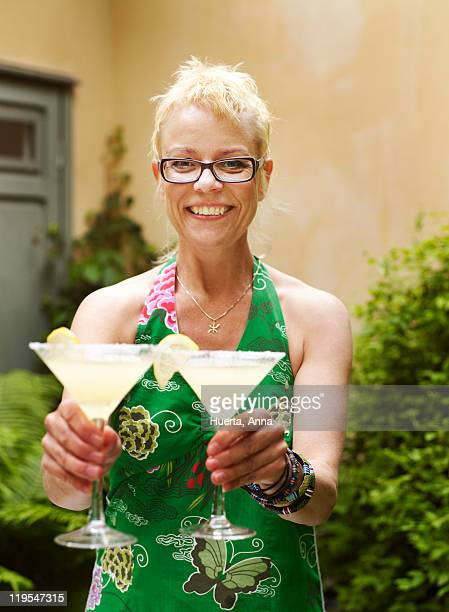 Woman holding cocktails, smiling