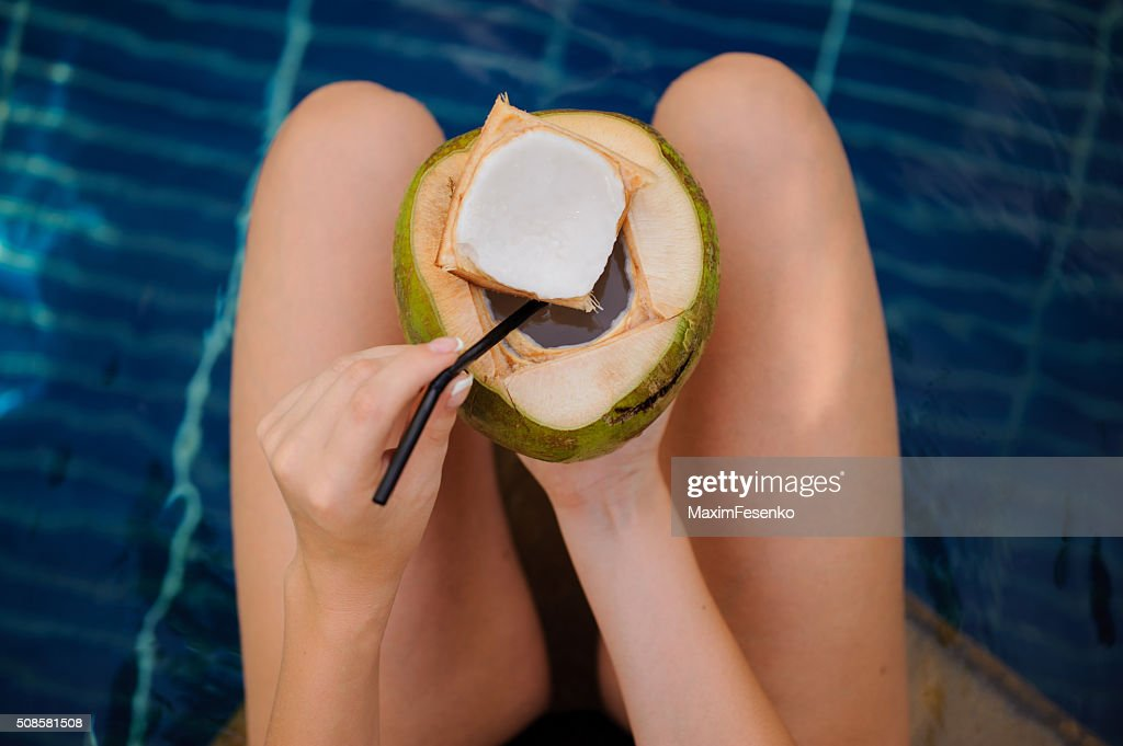 woman holding coconut  in the swimming pool : Stockfoto