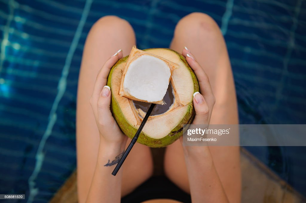 woman holding coconut  in the swimming pool : Stock Photo
