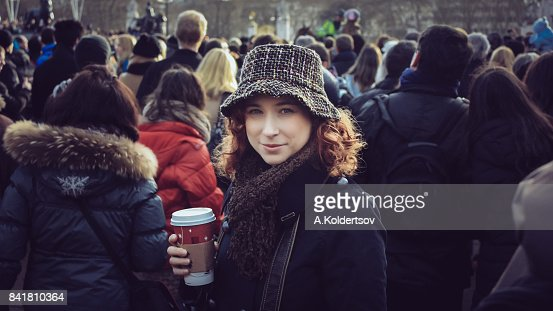 Woman holding coffee cup and looking at camera among tourists crowd next to Buckingham palace during Christmas holidays