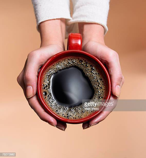 'Woman holding coffee cup, close-up, overhead view'