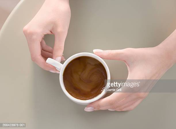 Woman holding coffee cup on table, close-up, overhead view