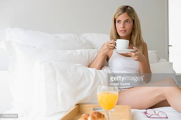 woman holding coffee cup - saucer stock pictures, royalty-free photos & images