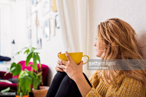 woman holding coffee cup while sitting against wall - warm clothing stock pictures, royalty-free photos & images