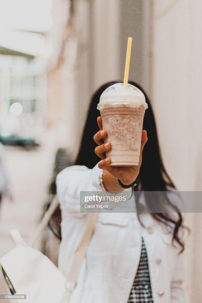 woman holding coffee milkshake at the street : Stock Photo