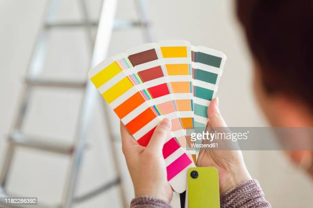 woman holding colour sample in an empty room with a ladder - color swatch stock pictures, royalty-free photos & images