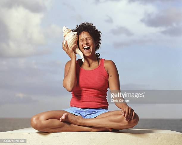 Woman holding conch shell to ear, laughing