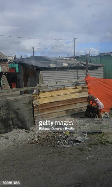 Woman Holding Container By Slum Houses