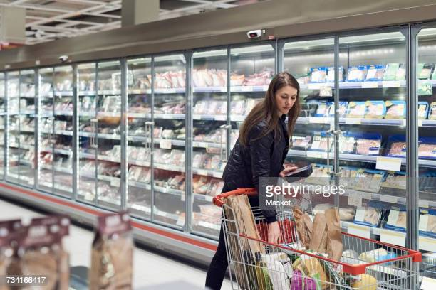 Woman holding container while standing by shopping cart at refrigerated section in supermarket