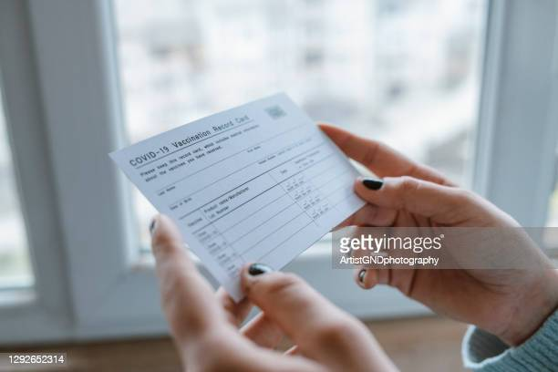 woman holding covid-19 vaccination record card. - anti vaccination stock pictures, royalty-free photos & images