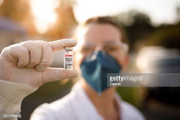 woman holding covid-19 vaccine vial - dose stock pictures, royalty-free photos & images