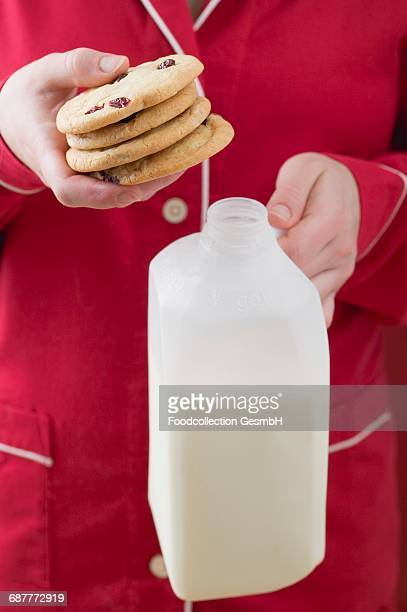 Woman holding cranberry cookies and bottle of milk