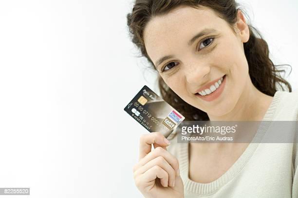 Woman holding credit card, smiling at camera