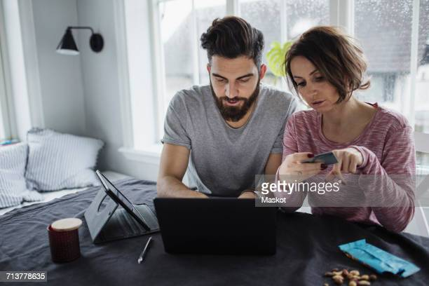 Woman holding credit card while man using laptop on table at home