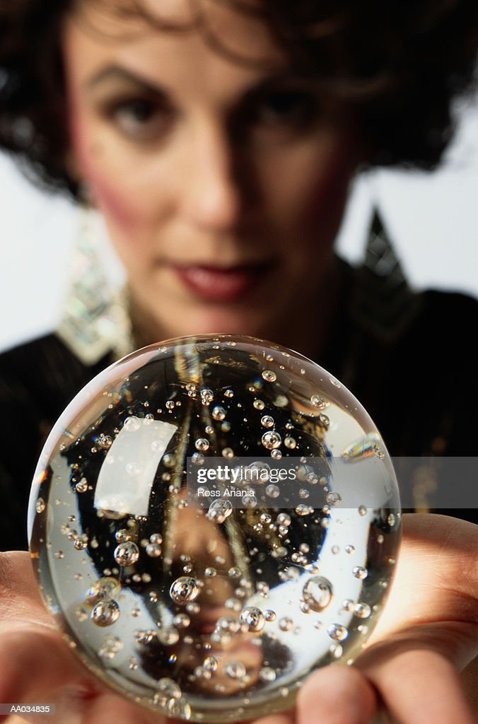 Woman holding crystal ball, close-up (focus on ball) : Stock Photo