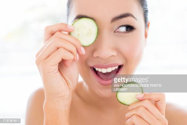 Woman holding cucumber in front of eye