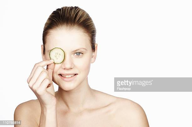 Woman holding cucumber over her eye