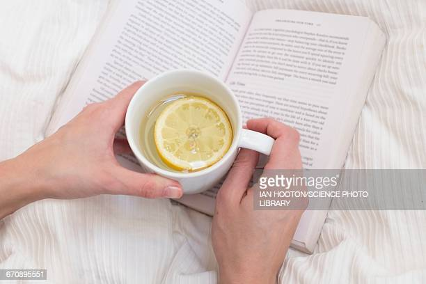 Woman holding cup and book