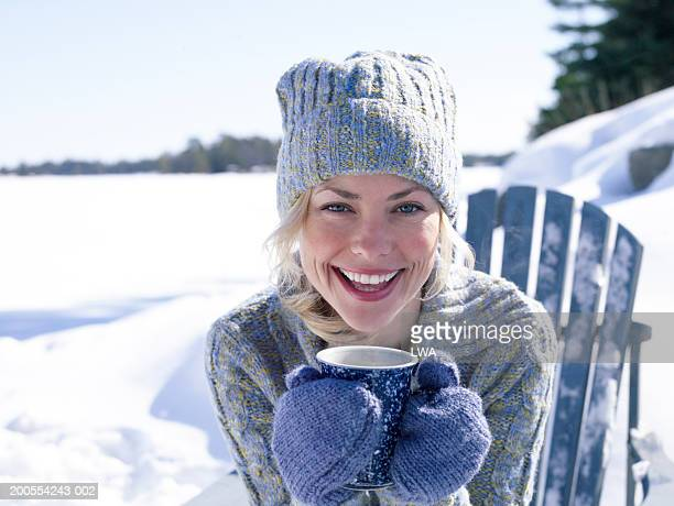 Woman holding cup in snow, smiling, close-up, portrait