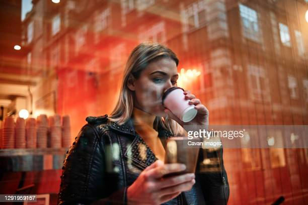 woman holding cup of coffee and smart phone in cafeteria. people and work concept. coffee shop. - drinking stock pictures, royalty-free photos & images