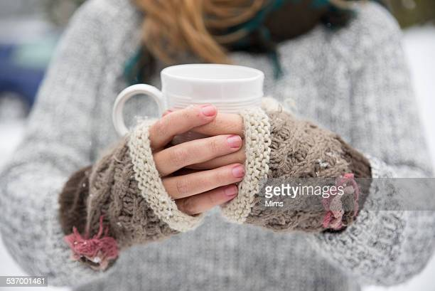 Woman holding cup of tea outdoors in snow