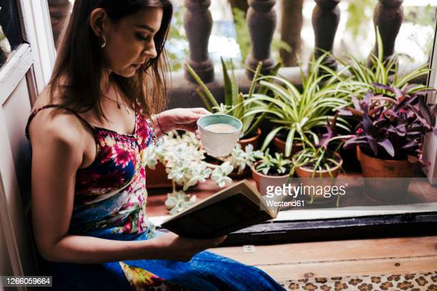 woman holding cup while reading book by balcony at home - mid adult women stock pictures, royalty-free photos & images