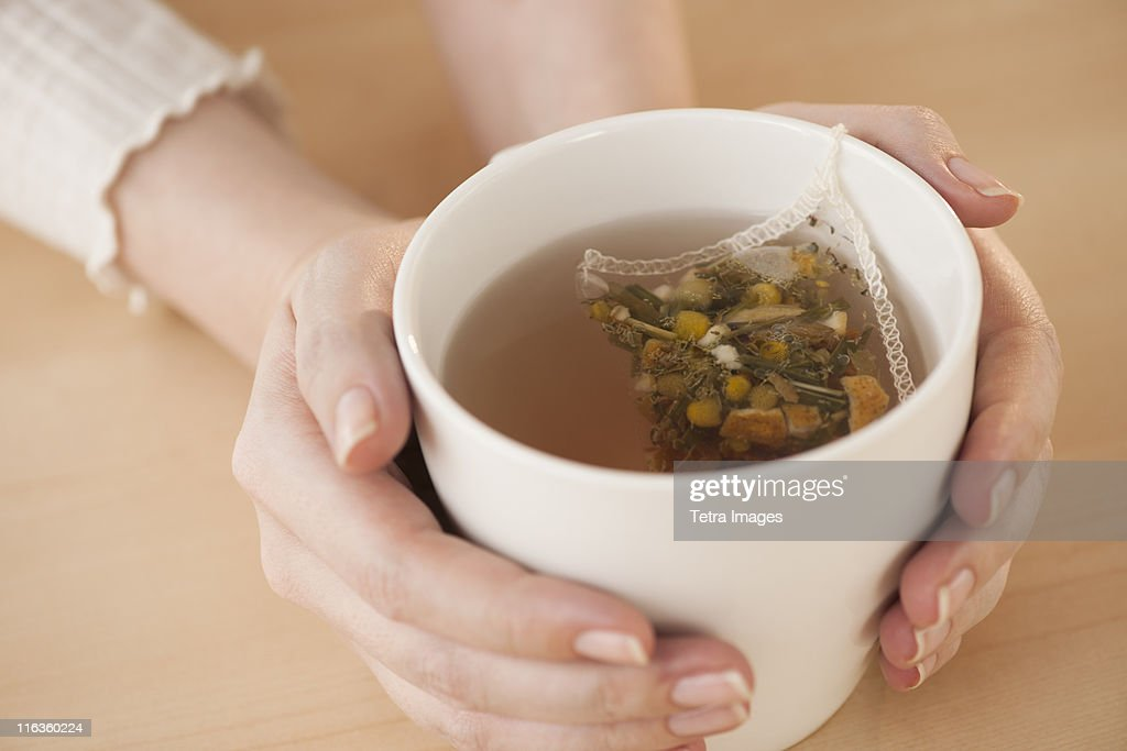 Woman holding cup with chamomile tea : Stock Photo