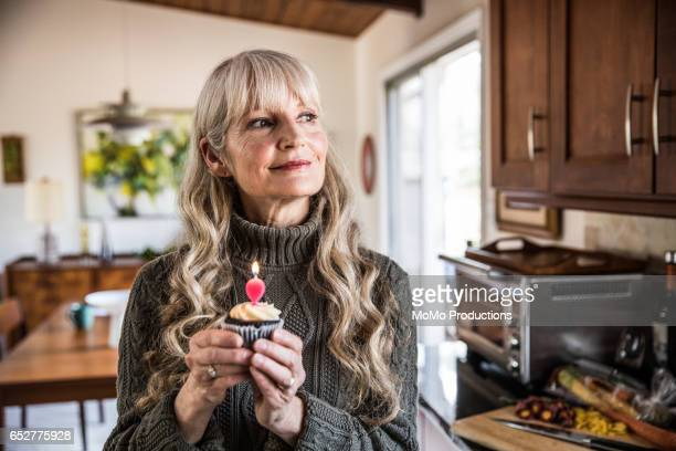 woman (60yrs) holding cupcake with birthday candle - woman birthday stock pictures, royalty-free photos & images