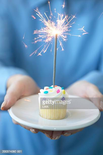 Woman holding cupcake with fire cracker, close-up