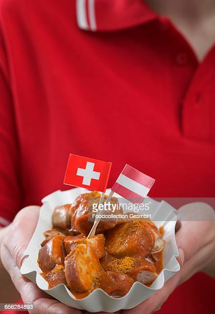 woman holding currywurst with two flags in paper dish - fat soccer players foto e immagini stock