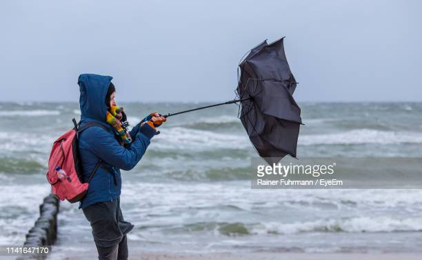 woman holding damaged umbrella while standing at shore of beach against sky - orkan stock-fotos und bilder