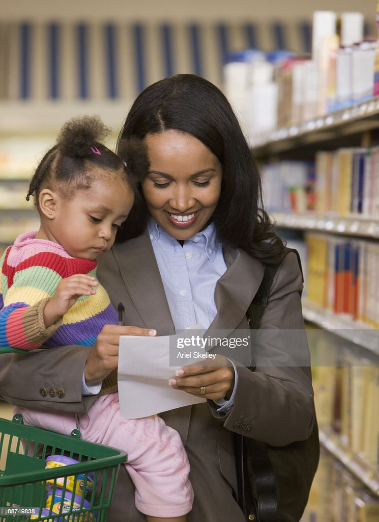 woman holding daughter and shopping list at grocery store stock