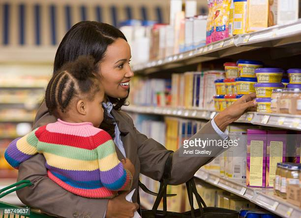 Woman holding daughter at grocery store