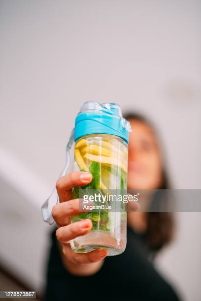 woman holding detox water bottle in her hand and trying to be healthy - infused water stock pictures, royalty-free photos & images