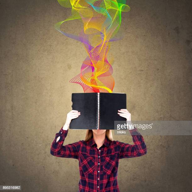 Woman holding diary in front of her face