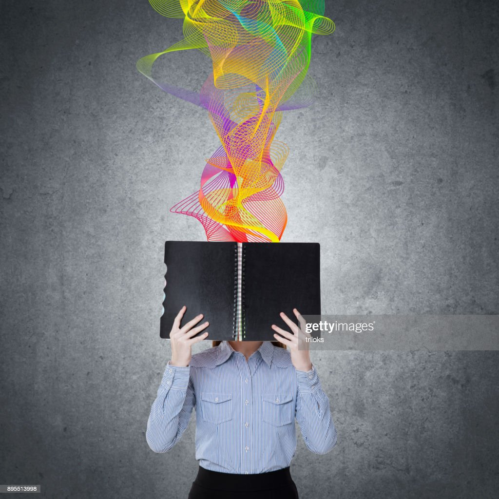 Woman holding diary in front of her face : Stock Photo