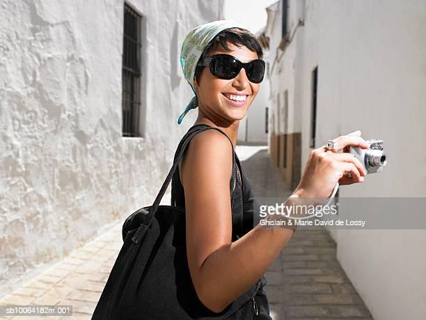 Woman holding digital camera in narrow street