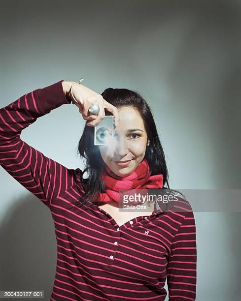 Woman holding digital camera, portrait