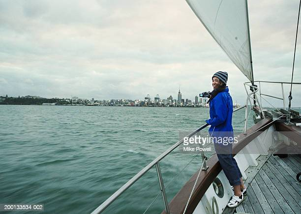 Woman holding digital video camera on bow of sailboat, portrait
