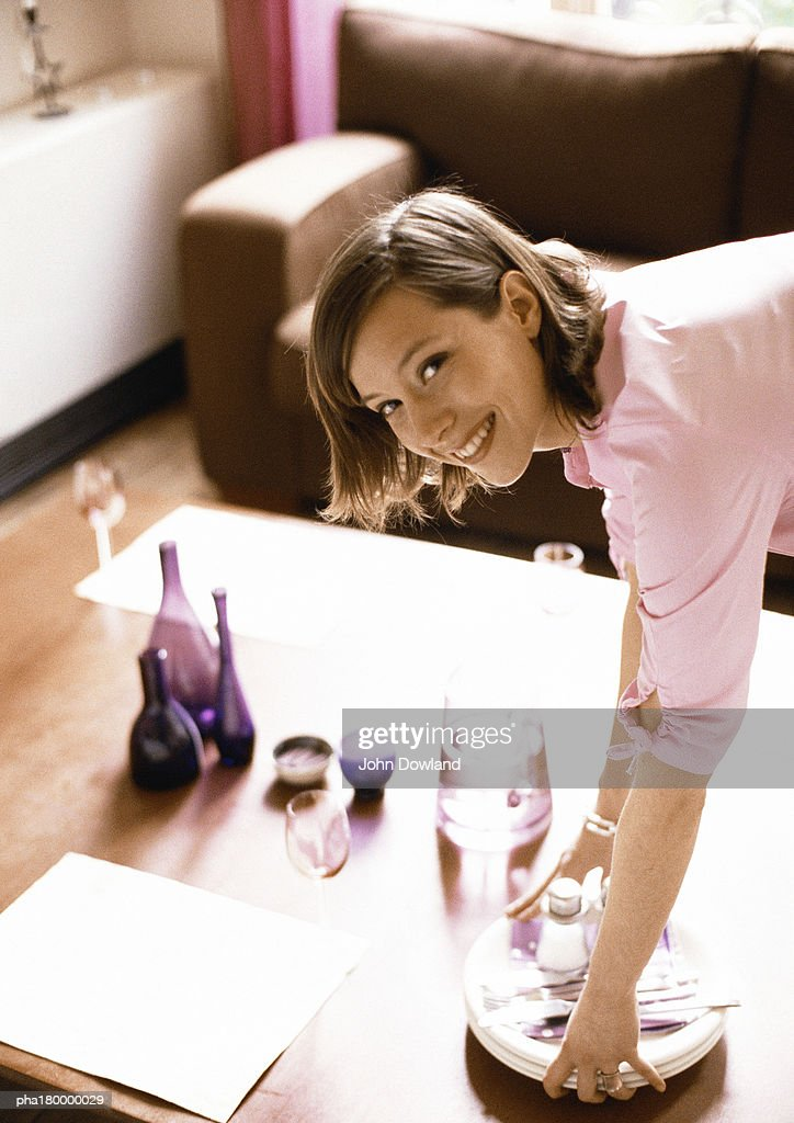 Woman holding dishes and silverware, smiling, portrait : Stockfoto