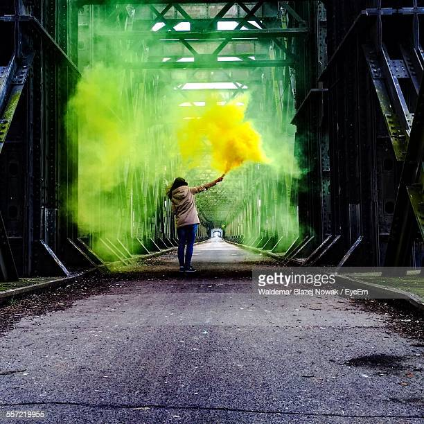 Woman Holding Distress Flare At Bridge