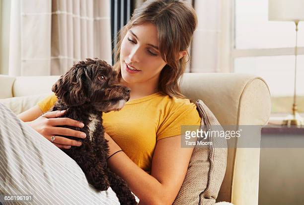 woman holding dog on sofa