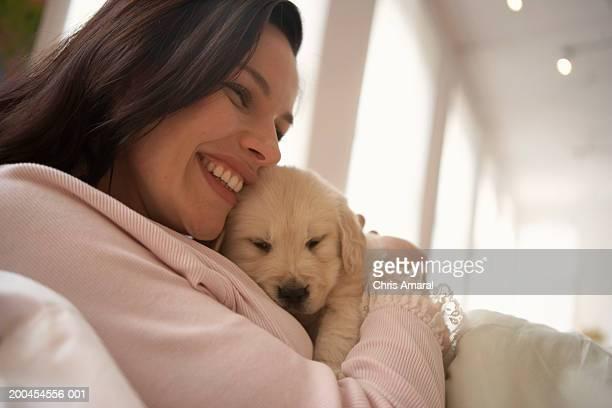 Woman holding dog, smiling