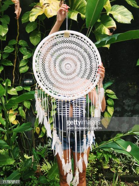 Woman Holding Dreamcatcher While Standing Against Plants At Yard