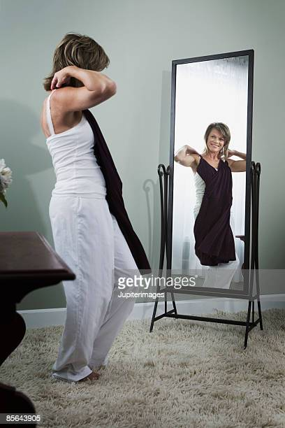 Woman holding dress and looking in mirror